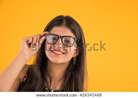 attractive young indian girl with eye glasses, indian lady wearing spectacles, closeup of asian girl with clear glasses - stock photo