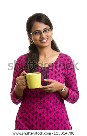 Attractive young Indian woman is showing green cup of aroma tea over white background - stock photo