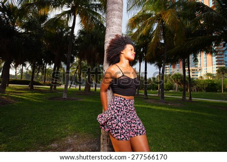 Attractive young Jamaican female posing in the park by a palm tree - stock photo