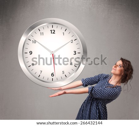 Attractive young lady holding a huge clock - stock photo