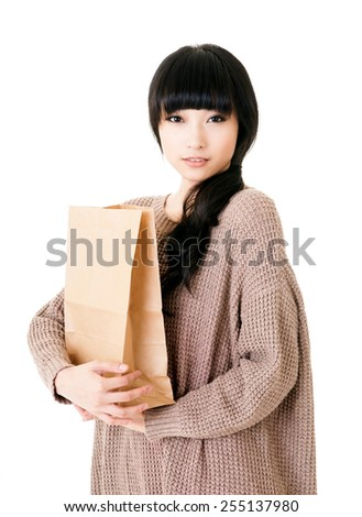 Attractive young lady holding paper bag, closeup portrait. - stock photo