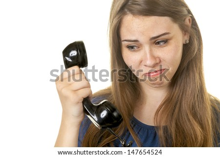 Attractive young lady looking oddly at an antique telephone.