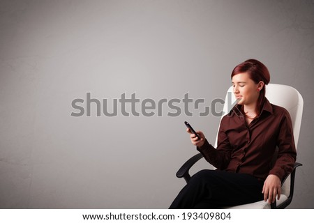 attractive young lady sitting and holding a phone with copy space - stock photo