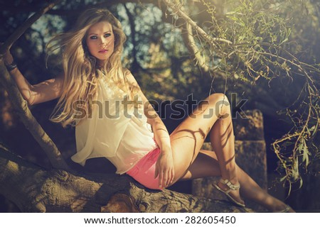 attractive young lady sitting on a branch - stock photo