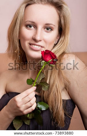 Attractive young lady with a red rose - stock photo