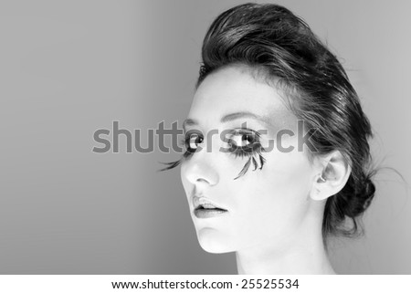 Attractive young lady with extravagant makeup and eyelashes closeup of head