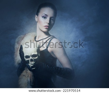 Attractive young lady with the scull over the smoky background - stock photo
