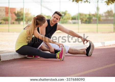 Attractive young Latin couple stretching their legs together before going for a run outdoors - stock photo