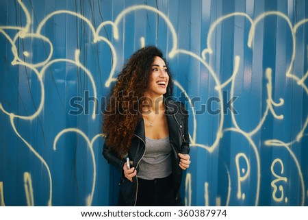 Attractive young laughing girl with long curly hair wearing a black leather jacket posing on a background of blue wall with graffiti - stock photo