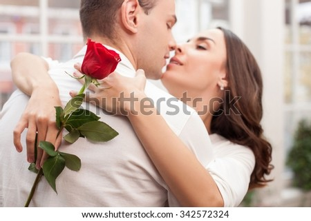 Attractive young loving couple is celebrating their anniversary. They are kissing with love. The man and woman are standing and embracing. The lady is holding a red rose - stock photo