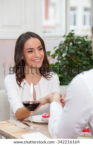 Attractive young loving couple is dating at the restaurant. They holding hands and smiling. The man and woman are drinking wine and eating dessert - stock photo
