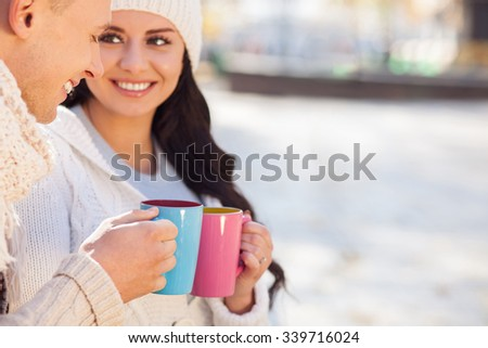 Attractive young loving couple is drinking tea outdoors. They are clicking their cups and smiling. The man and woman are sitting and looking at each other with love. Copy space in right side - stock photo