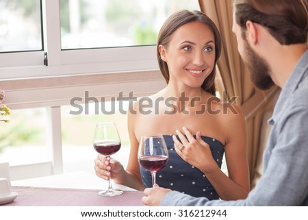 Attractive young loving couple is talking and smiling in restaurant. They are sitting and drinking red wine. The couple is looking at each other with love. There is a gold ring on female finger - stock photo