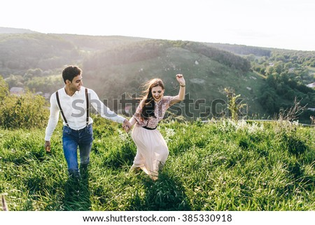 Attractive young loving couple of man in white shirt and blue jeans with backpack and gentle girl in dress standing on sunny outdoor background in the green mountain landscape