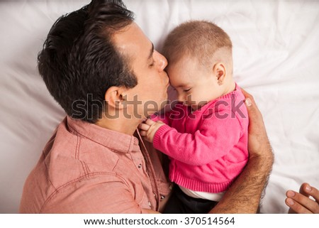 Attractive young loving dad lying on a bed with his daughter and kissing her in the forehead - stock photo
