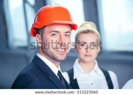 Attractive young male architect and his female assistant are working on plan of building. They are standing and holding a blueprint. The man is smiling. The woman is looking at camera seriously - stock photo