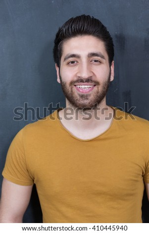 Attractive young man against blackboard. - stock photo