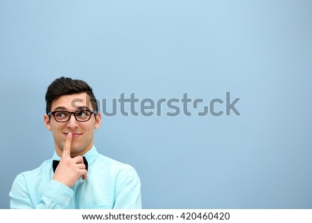 Attractive young man  against light blue wall - stock photo
