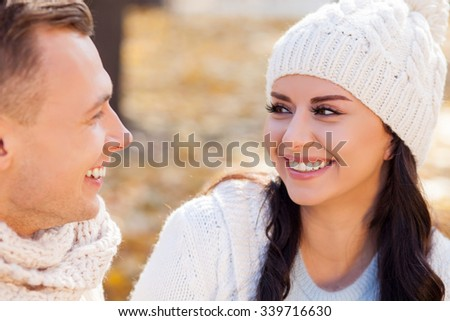 Attractive young man and woman are dating in the autumn park. They are looking at each other and smiling with love - stock photo