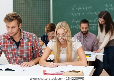 Attractive young man and woman studying together at their desks in a college or university classroom with other students and a blackboard behind them - stock photo