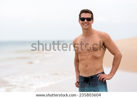 attractive young man at the beach - stock photo