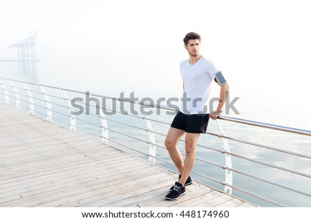 Attractive young man athlete with armband and cell phone standing on pier - stock photo
