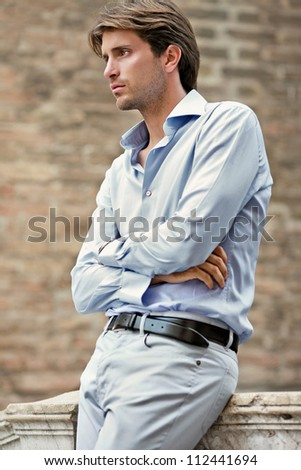 attractive young man awaiting on the bridge - stock photo