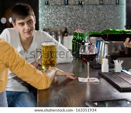 Attractive young man chatting to his girlfriend over a beer at the bar smiling as he listens to her talking, view from behind the woman with only her arm visible - stock photo