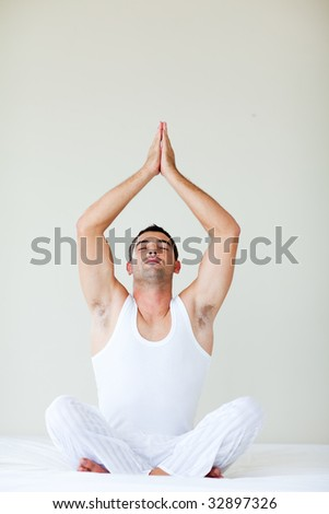 Attractive young man doing meditation in bed with copy-space - stock photo