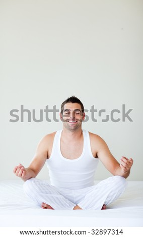 Attractive young man doing yoga in bed with copy-space - stock photo