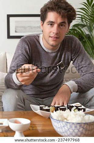 Attractive young man enjoying eating Japanese sushi and maki food at home, sitting on a white couch in a home living room, smiling relaxing on a sofa at home. Healthy man eating fresh food. - stock photo