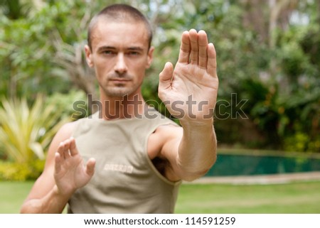Attractive young man focused on doing his martial arts training in a tropical garden.