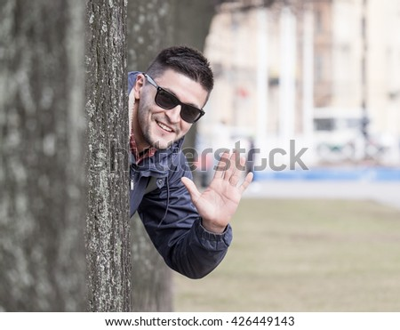 Attractive young man hiding behind the tree, smiling and wearing sunglasses in city park at spring