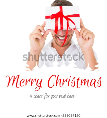 Attractive young man holding a gift against merry christmas - stock photo