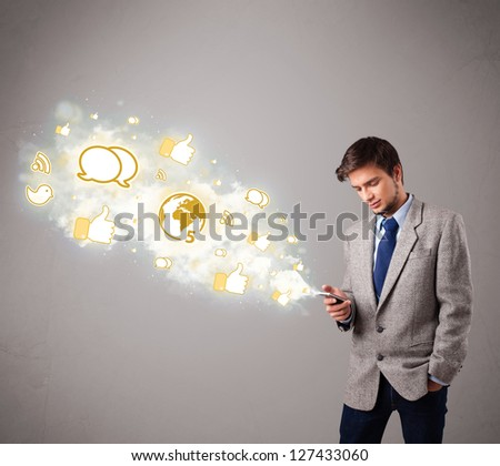 attractive young man holding a phone with social media icons in abstract cloud - stock photo
