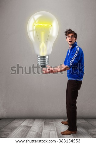 Attractive young man holding realistic 3d light bulb