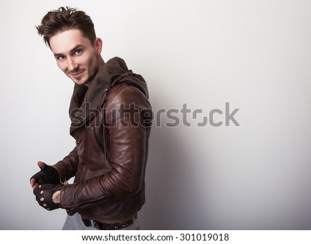 Attractive young man in a brown leather jacket pose in studio.  - stock photo