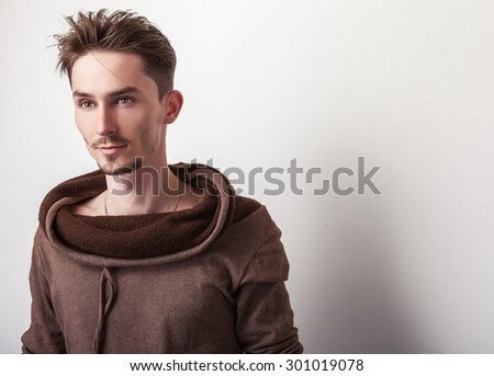Attractive young man in a brown sweater pose in studio.  - stock photo