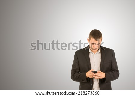 Attractive young man in a suit jacket standing texting on his mobile phone with a serious expression in a communications concept, on grey with copyspace