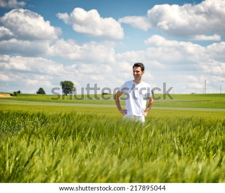 Attractive young man in a white t-shirt standing in a field of young green wheat enjoying nature and a sunny summer day with white clouds in a blue sky - stock photo