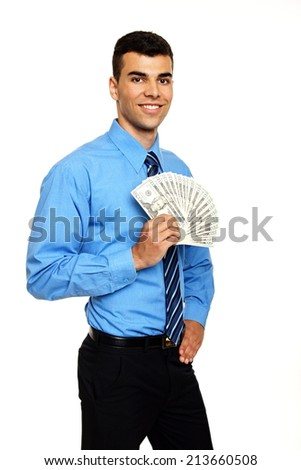 Attractive young man in blue shirt holds money in hand - stock photo