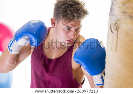 Attractive young man in boxing position hitting a punching bag - stock photo