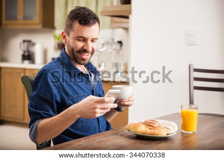 Attractive young man in denim shirt texting on his smartphone while having breakfast at home - stock photo