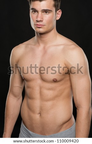 Attractive young man in front of black background - stock photo
