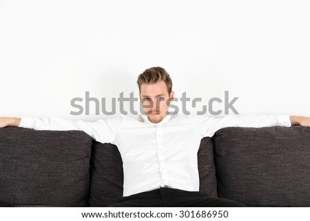Attractive young man in his 20s sitting down in a sofa, wearing a white shirt and black jeans. Feeling relaxed leaning back.  - stock photo