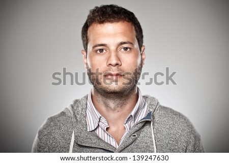 Attractive young man in studio looking at camera/Portrait of a normal boy over grey background. - stock photo