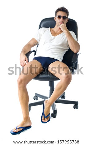 Attractive young man in t-shirt, with naked legs on office chair, isolated on white background - stock photo
