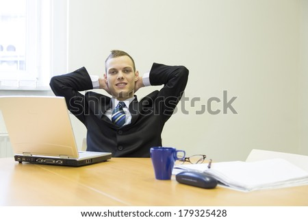 attractive young man in the office with laptop and folder