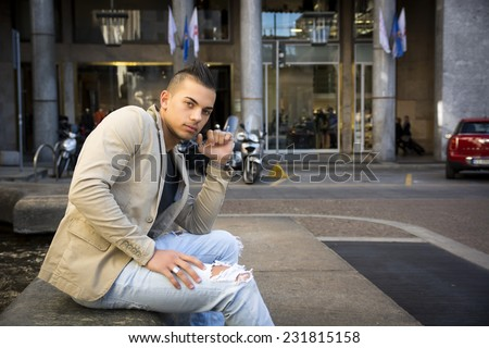 Attractive young man in urban setting, sitting on marble in city square, large copyspace - stock photo