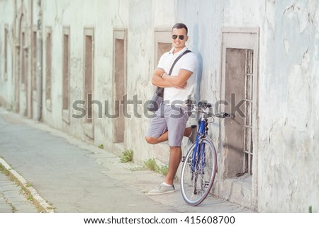 Attractive young man is standing on the street with his bicycle beside him. He is leaning on the wall of the old building and looking at camera. - stock photo